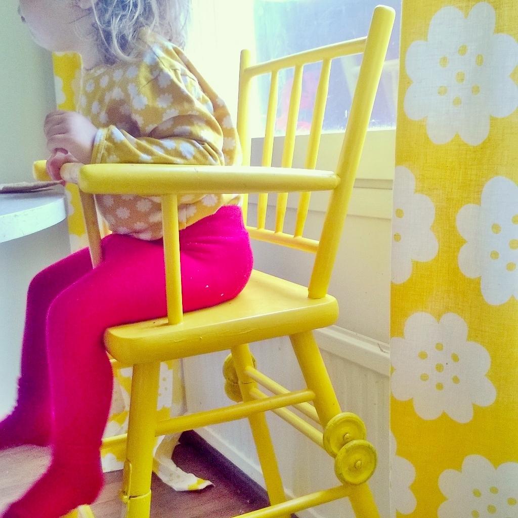 Elluyellow tytär keltaisessa retro syöttötuolissa.