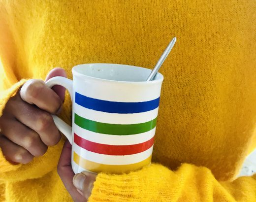 Elluyellow värikäs kahvikuppi ja keltainen villapaita